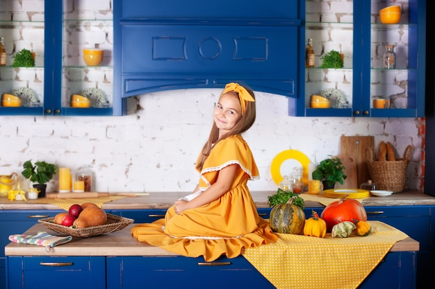 Bambina in abito giallo in autunno decor con zucche in cucina, vacanze di halloween. raccolta. sana alimentazione, vegetarismo, vitamine, verdure. Foto Premium