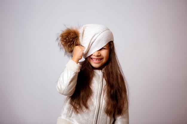 Bambina in cappello di inverno che sorride sul bianco Foto Premium