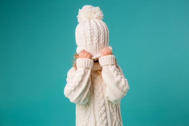 Bambina in inverno cappello e maglione lavorato a maglia Foto Premium