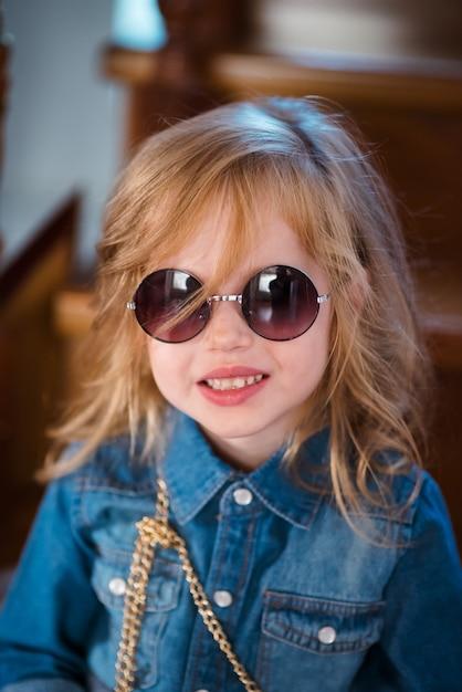 Bambina in jeans camicia e occhiali da sole in posa e sorridente. Foto Premium