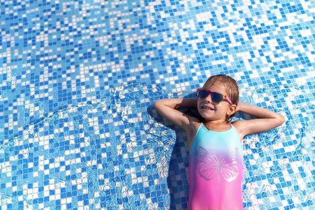 Bambina in occhiali da sole e cappello con unicorno nella piscina all'aperto del resort di lusso in vacanza estiva sull'isola tropicale della spiaggia Foto Premium