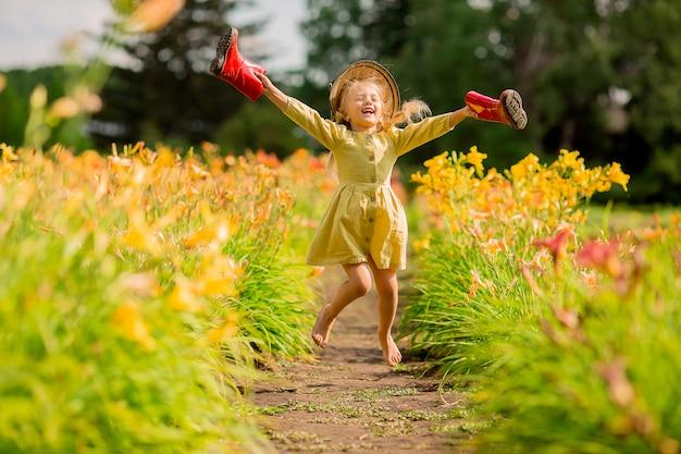 Bambina in stivali di gomma rossi e un cappello di paglia che innaffia i fiori d'innaffiatura rossi nel giardino Foto Premium