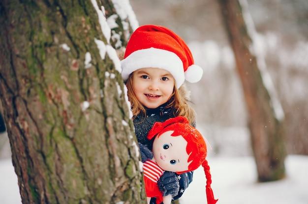 Bambina in un cappello blu che gioca in una foresta di inverno Foto Gratuite