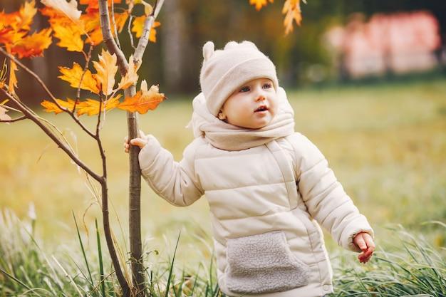 Bambina in un parco in autunno Foto Gratuite