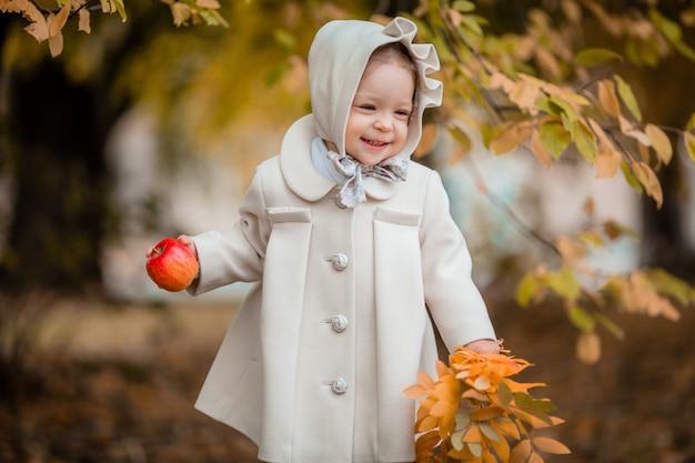 Bambina in una passeggiata nel parco in autunno Foto Premium