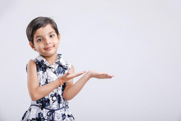 Bambina indiana che mostra qualcosa con le sue mani. copyspace Foto Premium