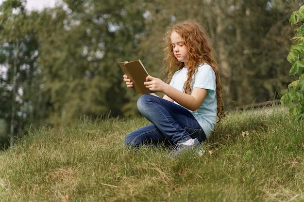 Bambina intelligente che legge il libro all'aperto. Foto Premium
