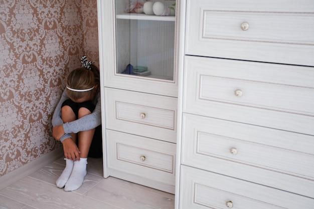 Bambina lesa seduta in un angolo della sua stanza Foto Premium