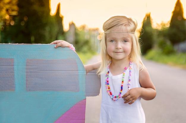 Bambina nello stile di hippy che sta all'aperto sulla strada vicino all'automobile Foto Premium
