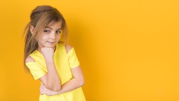 Bambina premurosa in vestito su priorità bassa gialla Foto Gratuite