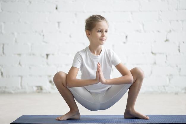 Bambina ragazza in posa di malasana, sfondo bianco dello studio Foto Gratuite