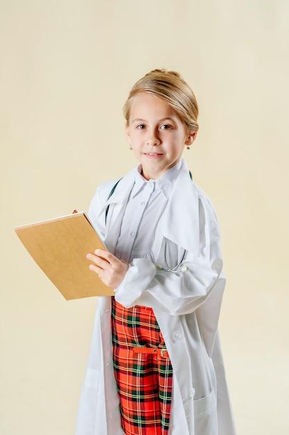 Bambina sorridente adorabile vestita come medico con lo stetoscopio isolato Foto Premium