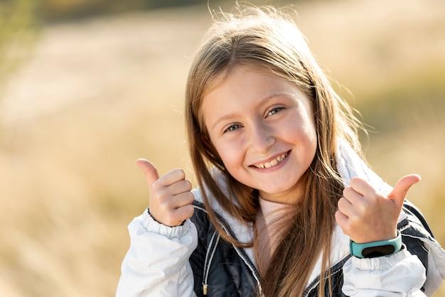 Bambina sorridente che mostra segno giusto Foto Gratuite