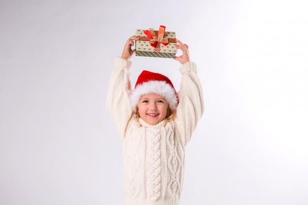 Bambina sorridente in santa cappello tenendo confezione regalo su sfondo bianco Foto Premium