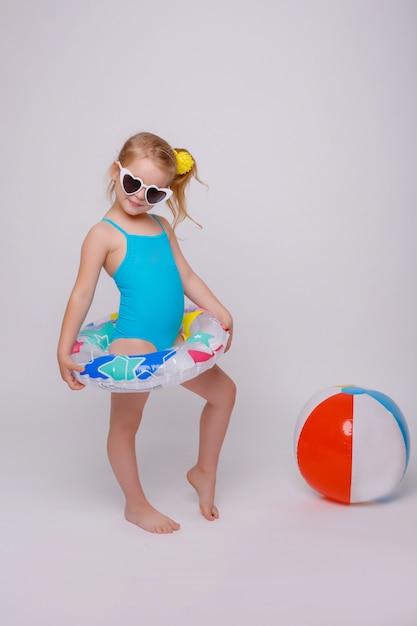 Bambina sorridente sveglia in costume da bagno con l'anello di gomma isolato su bianco Foto Premium