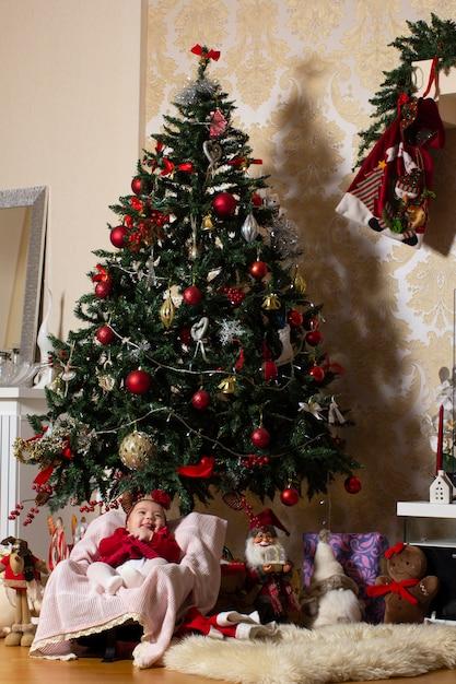 Bambina sotto l'albero di natale con i giocattoli farciti