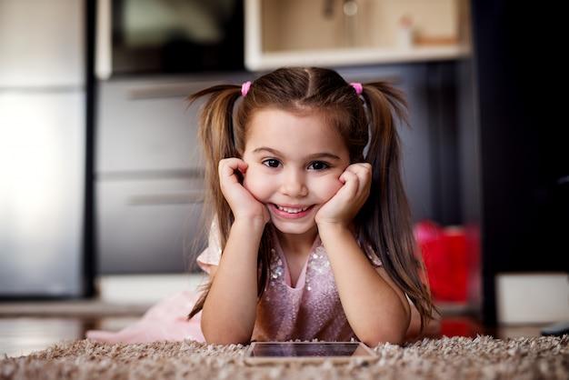Bambina sveglia che esamina macchina fotografica e che tiene compressa. ritratto di bel bambino. Foto Premium
