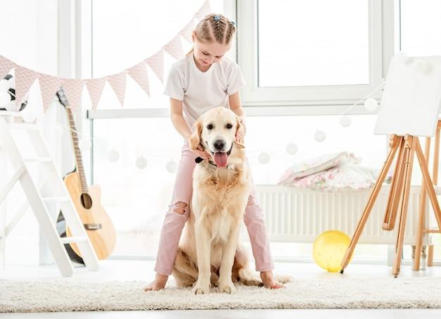 Bambina sveglia che gioca con il cane Foto Premium