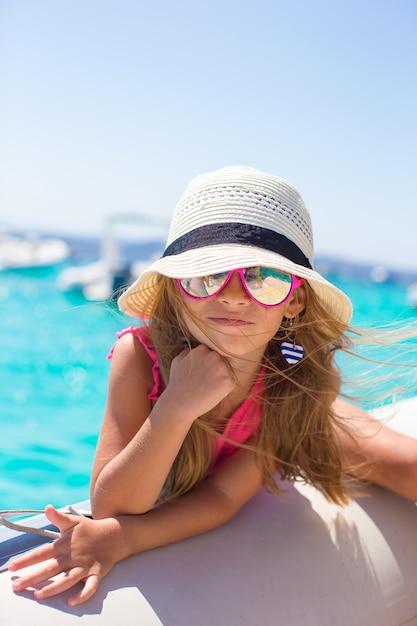 Bambina sveglia che gode della navigazione sulla barca nel mare aperto Foto Premium