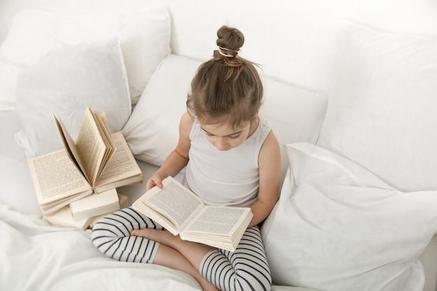 Bambina sveglia che legge un libro sul letto nella camera da letto. Foto Gratuite