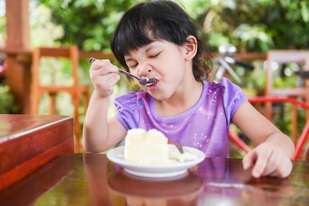 Bambina sveglia che mangia torta Foto Premium