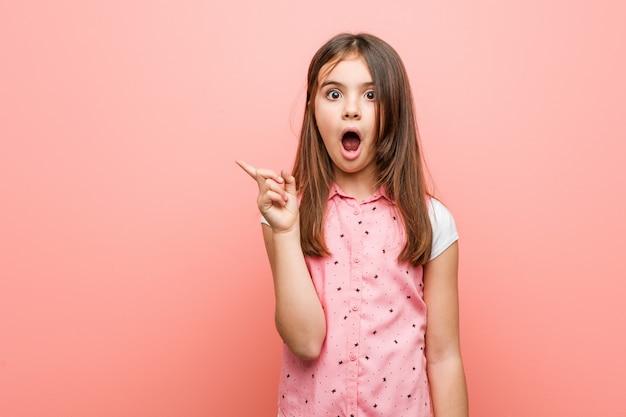 Bambina sveglia che punta verso il lato Foto Premium