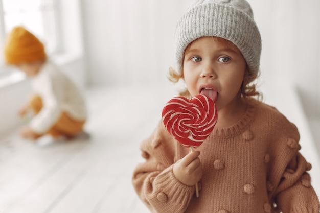 Bambina sveglia che si siede e che mangia caramella Foto Gratuite