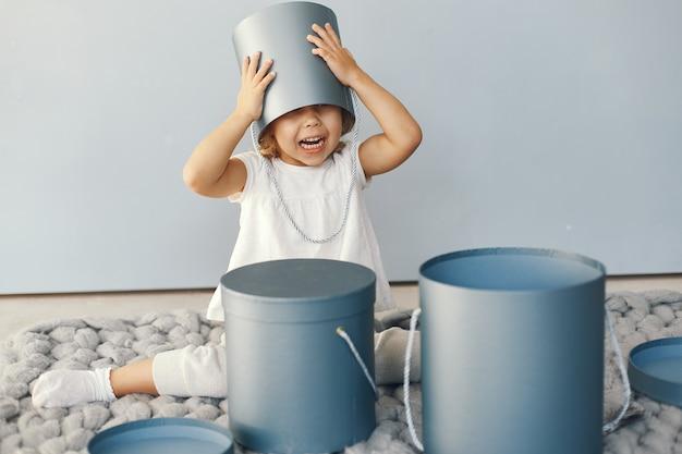Bambina sveglia che si siede in uno studio con la scatola dei presente Foto Gratuite