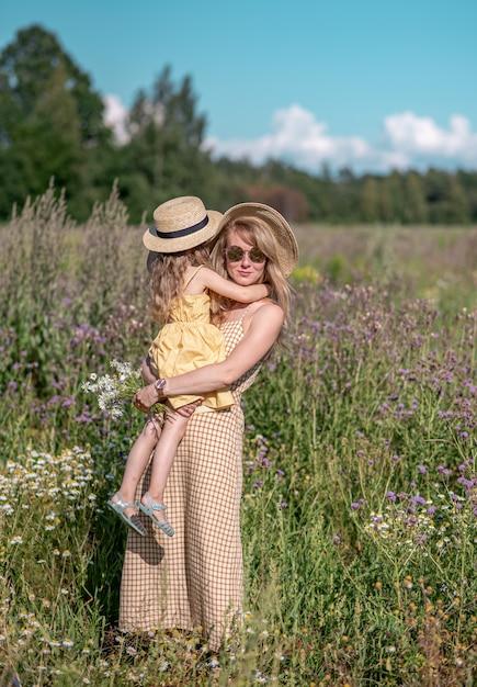 Bambina sveglia con sua madre che cammina nel giacimento di fiori Foto Premium
