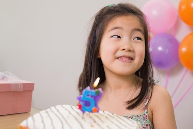 Bambina sveglia con torta alla sua festa di compleanno Foto Premium