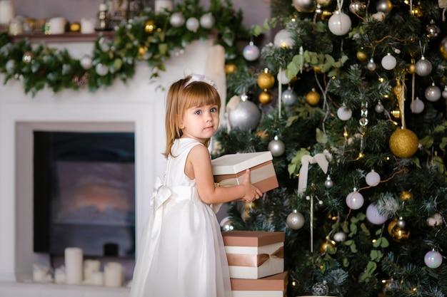 Bambina sveglia in abito bianco con grandi regali vicino all'albero di natale Foto Premium