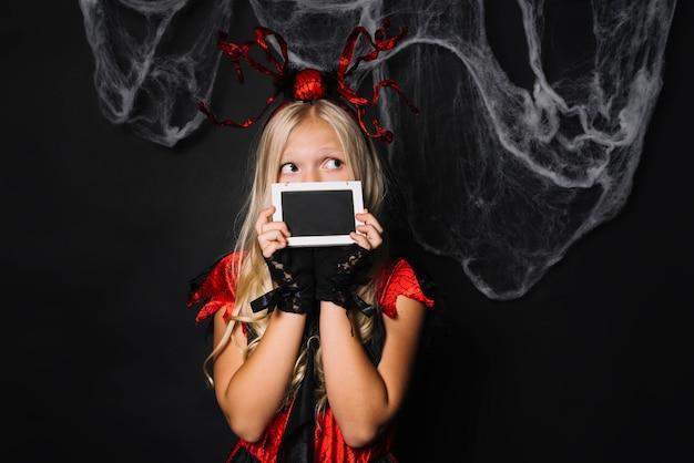Bambina sveglia in costume rosso che sta con l'insegna Foto Gratuite