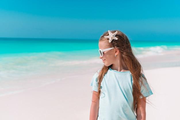 Bambina sveglia in spiaggia durante le vacanze estive Foto Premium