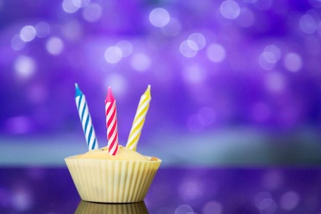 Bambina sveglia in vestito elegante che celebra il giorno di compleanno con palloncini viola Foto Premium