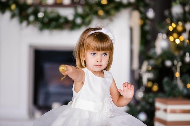 Bambina sveglia nel vestito bianco con bella corona vicino all'albero di natale Foto Premium