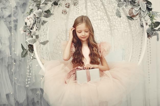 Bambina vicino all'albero di natale in un vestito rosa Foto Gratuite