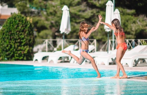 Bambine adorabili che giocano nella piscina all'aperto in vacanza Foto Premium