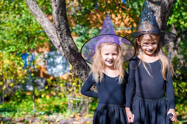 Bambine adorabili in costume della strega su halloween all'aperto Foto Premium