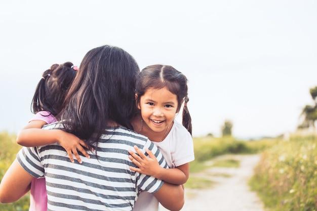 Bambine asiatiche felici che abbracciano madre e divertirsi a giocare con la madre Foto Premium