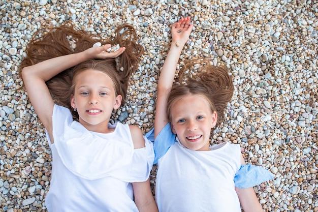 Bambine che si divertono alla spiaggia tropicale durante le vacanze estive Foto Premium