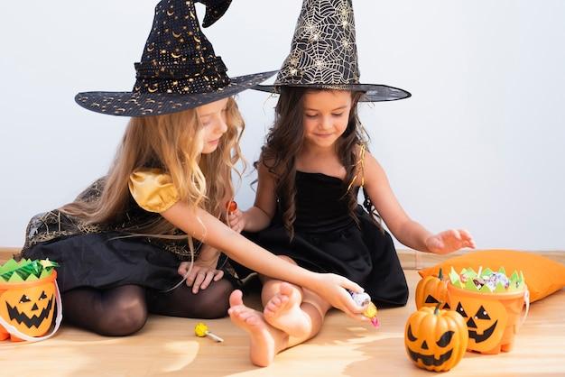 Bambine di vista frontale che si siedono sul pavimento su halloween Foto Gratuite