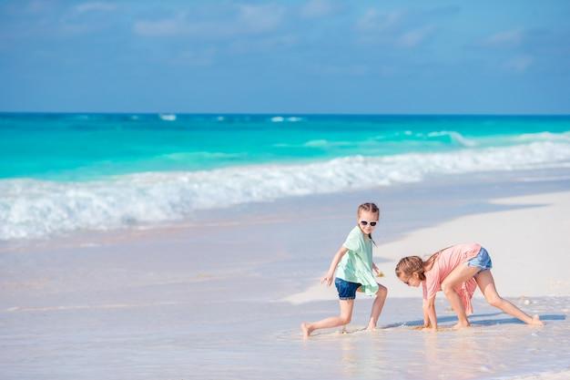 Bambine divertendosi alla spiaggia tropicale che gioca insieme alle acque basse Foto Premium