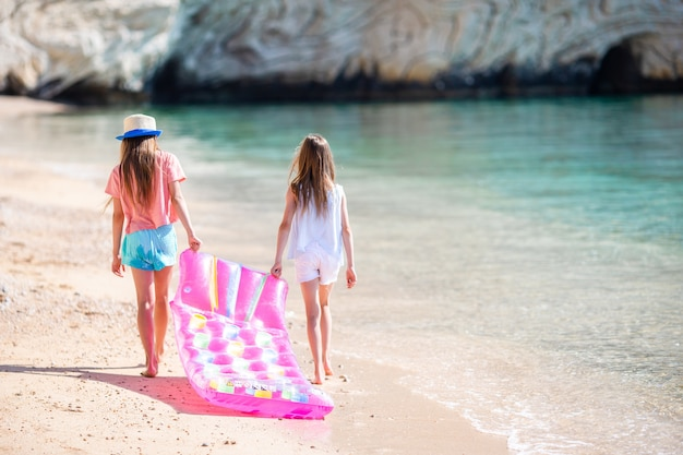 Bambine divertendosi alla spiaggia tropicale durante le vacanze estive che giocano insieme Foto Premium