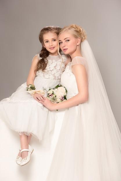 Bambine graziose con fiori vestiti in abiti da sposa Foto Gratuite
