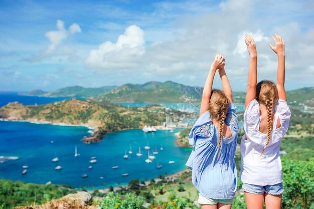 Bambini adorabili che godono della vista del porto inglese pittoresco all'antigua in mar dei caraibi Foto Premium