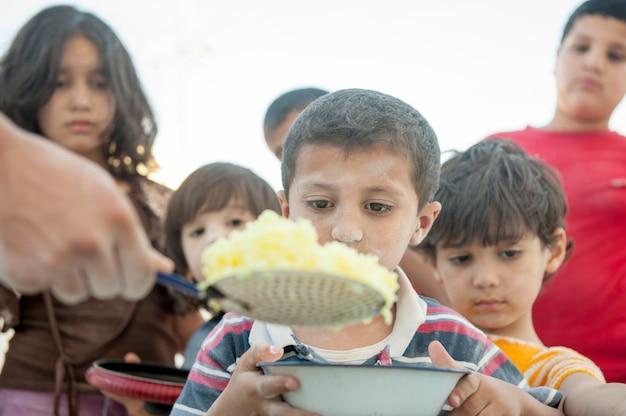 Bambini affamati nutriti dalla carità Foto Premium