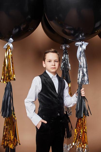 Bambini alla moda in abiti da sera e costumi che celebrano il primo giorno di scuola. festa per bambini Foto Premium