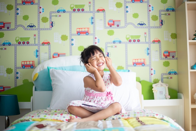 Bambini asiatici che utilizzano la cuffia per ascoltare musica da smartphone sul letto nella sua camera da letto decorata Foto Premium