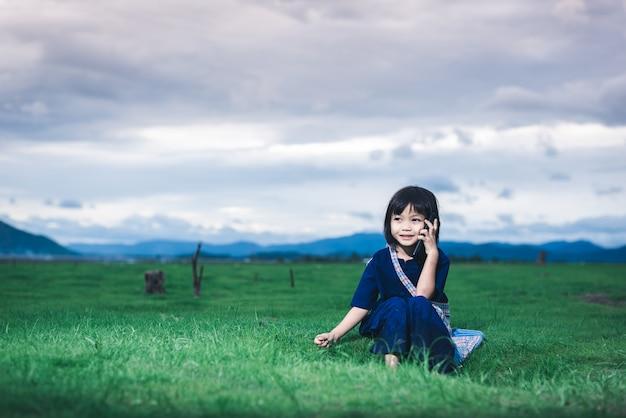 Bambini asiatici in abiti locali usano uno smartphone che chiama sua madre per prenderla in campo dopo aver finito di pescare Foto Premium
