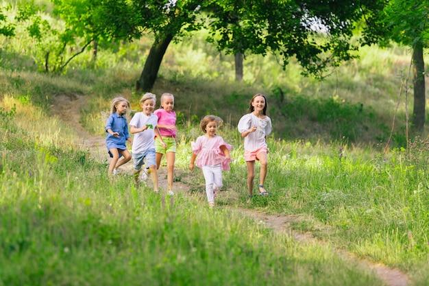 Bambini, bambini che corrono sul prato alla luce del sole estivo. Foto Gratuite